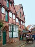 Backstein- und Fachwerkhaus in der Altstsadt von Lüneburg, davor ein Handwerkerstand und ein Schubkarren aus Holz.